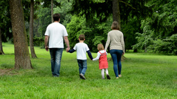 family (middle couple in love, cute girl and small boy) walking in park from cam Footage