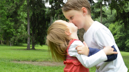 children (siblings - boy and girl) give a kiss in park Footage