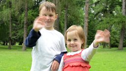 childrens (young boy and little girl (siblings)) wave with hands and smile to ca Footage