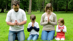 family (middle aged couple in love, boy and girl) pray in park (family kneeling  Footage