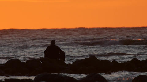 Slow motion, Man relaxing at the sea at sunset Footage