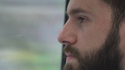 young handsome hipster man traveling by public transport and looks out of the wi Footage