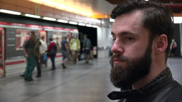 young handsome hipster man waits for subway and looks around - arriving metro -  Footage