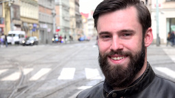 young handsome hipster man smiles to camera - city: urban street with passing ca Footage