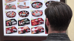 Young Handsome Hipster Man Looks At The Menu Of Restaurant With Sushi - Outside stock footage