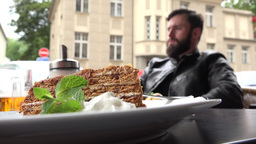 food - dessert - honey cake - young handsome man (hipster) sitting in background Footage