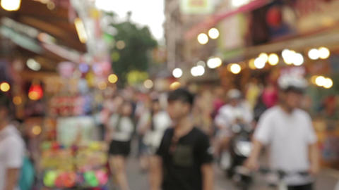 Out of focus people walking though a market Footage