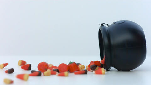 halloween candy spills out of a black caluldron in slow motion Footage
