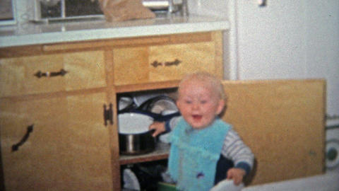 TOLEDO, OHIO 1968: Toddler boy playing with pots in kitchen cabinets Footage
