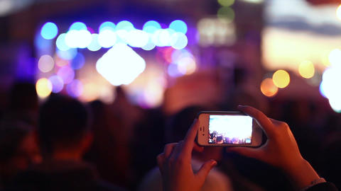 Hands hold cameras with digital displays among people at rock concert ビデオ