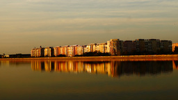 Urban landscape with lake at sunset and windows reflected in lake Footage