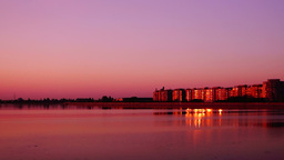 Urban landscape with lake at sunset.Cityscape at dusk with mirror-like lake Footage