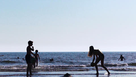 Children play with a ball in sea, sunset Footage