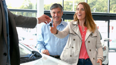 Couple taking keys from businessman Footage