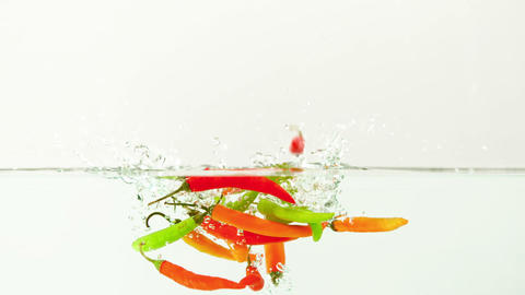 Chili peppers falling in water Footage