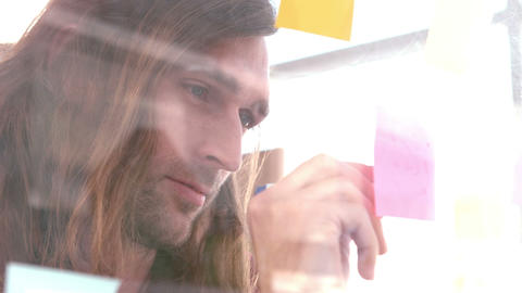 Businessman writing notes on a sticky note Footage
