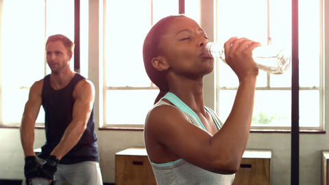 Fit woman drinking water in fitness studio Live Action