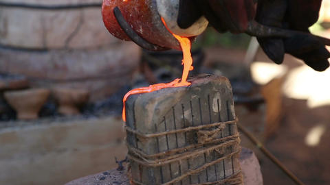 Blacksmith pours the molten metal from the heated crucible into the form for sme Footage