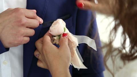 She attaches to the jacket of the groom boutonniere Footage
