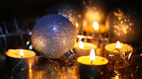Burning small candles and Christmas tree decorations against a dark background Footage