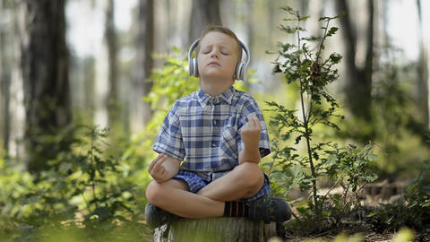 Little Boy Meditating In The Forest stock footage