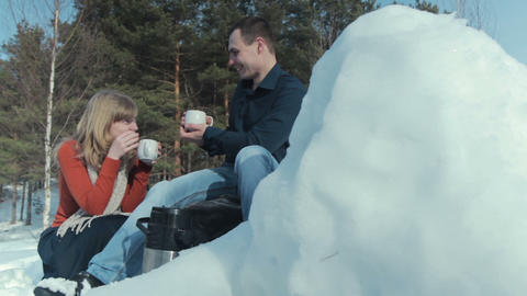 Young couple in love on a winter vacation enjoying the nature and drinking hot t Live Action