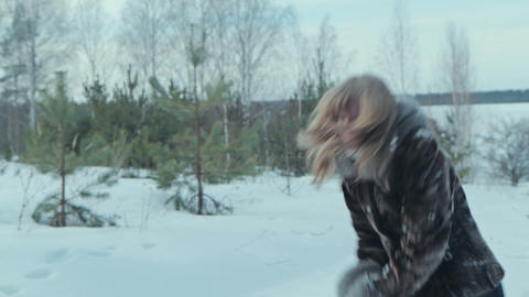 Couple having snowball fight in snow in winter forest Footage
