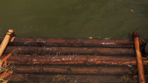 transparent river water washes out wooden logs of bank platform Footage