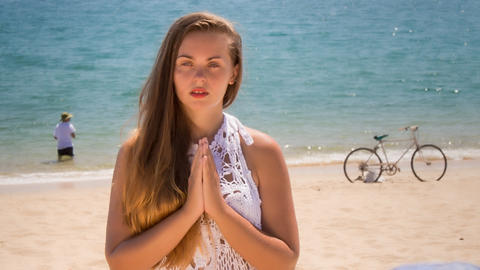 blonde girl in lace meditates in yoga asana on beach Footage