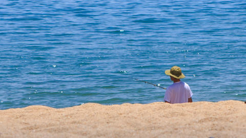fisherman in hat fishes with rod on sand beach against azure sea Footage