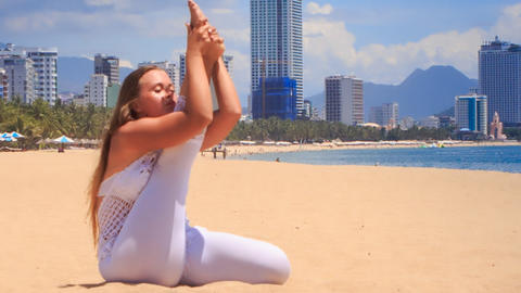 blonde girl in lace shows yoga asana stretching leg Footage