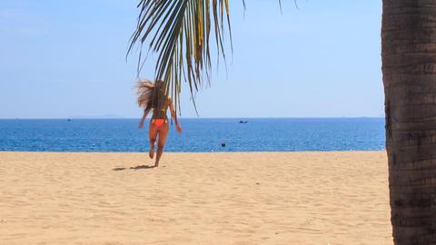 blonde slim gymnast in bikini backside runs to sea waves hands Footage