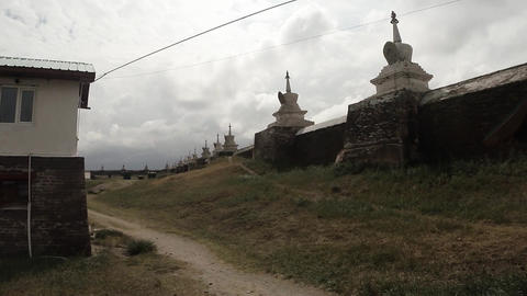 Wall of ancient monastery under the cloudy sky and Buddhist shrines Footage