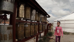 girl walks past a plurality of reels of old prayer mantras inscribed in Sanskrit Footage