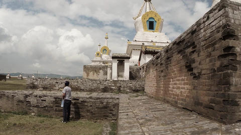 man throws grain white dove on sacred Buddhist temple in old building against th Footage