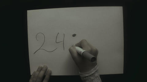 child's hand writing on a white sheet of a top view 24 : 4 = 6 ビデオ