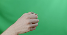 Men's Hand Lights A Cigarette Lighter On A Green Background stock footage