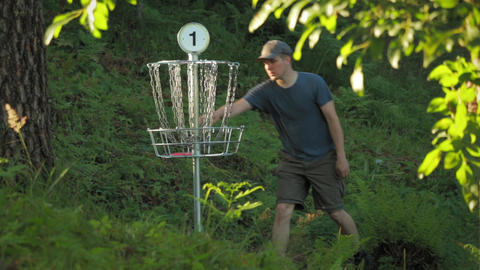Male disc golf player throws a putter in the basket and picks up the disc Footage