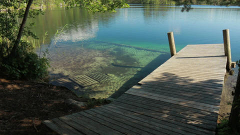 Panning shot of the shore of clear-watered lake Valkiajärvi with a wooden dock Live Action