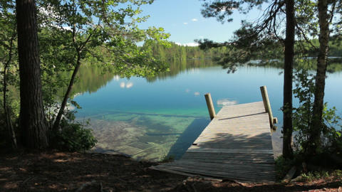 Shore of clear-watered lake Valkiajärvi with a wooden dock Live Action