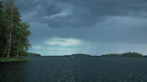 Wind growing stronger as rain clouds approach behind a lake Footage