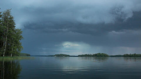 Rain clouds approaching behind a calm lake Footage