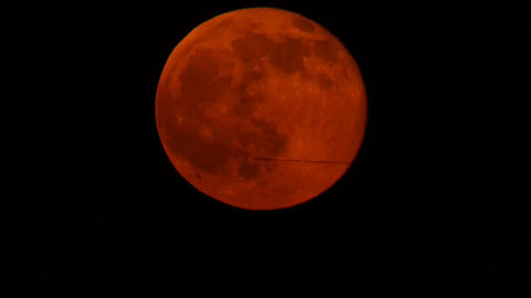 Plane crossing rising Blood Moon