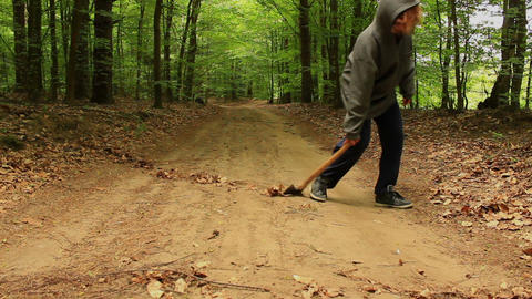 Hooded axeman dragging along an axe across the path in a forest Live Action
