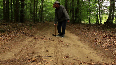 Hooded axeman dragging along the path an axe towards camera - accelerated Footage