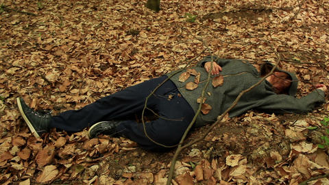 Dead or drunk woman lying on the ground among the withered leaves Footage