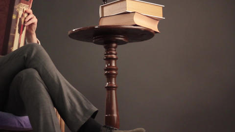 Man reads a book on the chair Footage