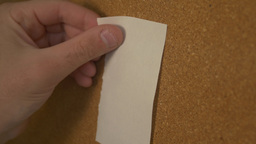 Pinning A Paper On Cork Board stock footage