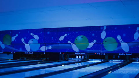 wide angle - balls miss pins at neon bowling Footage
