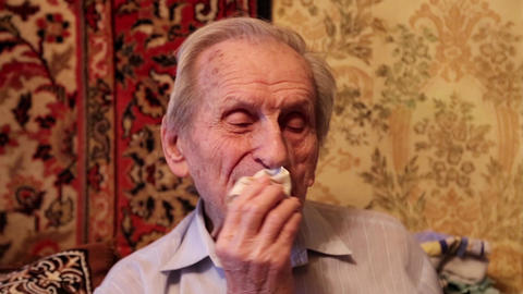 Grey-haired old man carefully wipes his lips after eating Footage